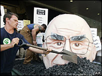Protesters bury an effigy of Australian Prime Minister John Howard in coal