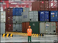 A worker stands in front of containers at China's new Yangshan deep water port