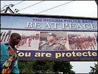 Man walks past Nigeria police poster