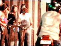 A motorcyclist rides past a group of young women hanging out near the Lumpini park in Bangkok in this photo taken in March 2000