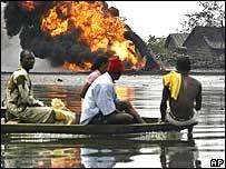 Men in a boat watch a burning oil pipeline in Nigeria