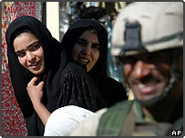 Iraqi women at market in Baghdad smile as Iraq soldier walks past