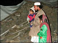 Shah Zaman and his family look at the wreckage of their home in Damadola