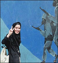 Iranian woman walks past nationalistic mural