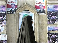 An Iraqi woman walks past election posters
