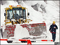 A bulldozer clears snow from a road in Niigata prefecture