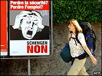 "A woman walks past a poster calling for a ""No"" vote in the Swiss referendum on Schengen"