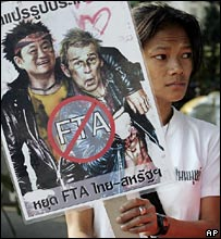 A Thai activist holds a banner of Thaksin Shinawatra and George Bush during a rally opposing the Thai-US free trade talks, 12 Jan 2006