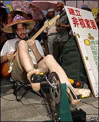 A protester uses pedal power to run his electric guitar at an environment rally in Taiwan