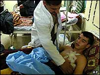 An Iraqi doctor treats a patient wounded in a bomb attack