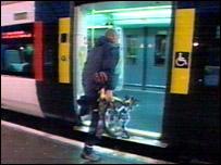 Man taking a folding bike onto a Southern train