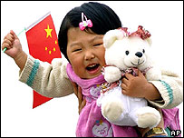 A child carries a toy bear and a flag on Beijing's Tiananmen Square