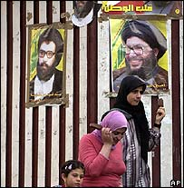 Lebanese women walk past posters showing Hezbollah chief Hassan Nasrallah