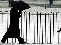 Person holding an umbrella to shield themselves from the elements, during a heavy snowfall in London