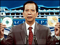 Presidential spokesman Ignacio Bunye displays a CD, left, which he claimed was a wiretapped cell phone call between President Arroyo and an election official, 06/06/2005.