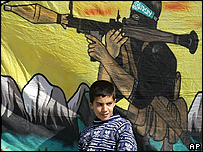 Boy stands in front of Hamas poster