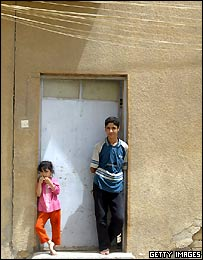 A brother and sister stand under electricity cables strung in front of their home in a neighborhood in Baghdad