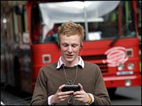 Man watching TV with bus in background