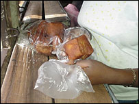 Rwandan trader wrapping cakes in plastic bags