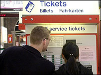 Couple buying tickets at London's Victoria Station