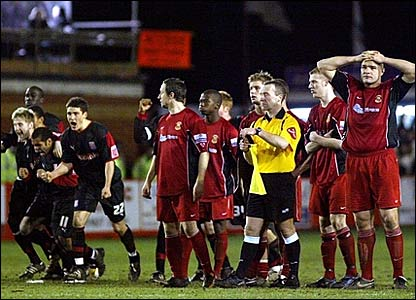Stoke players (left) celebrate their penalty shoot-out victory, while Tamworth's frustration is evident for all to see