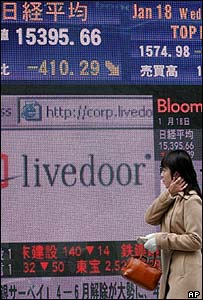 A woman walks past a screen showing the stock prices in Tokyo on Wednesday