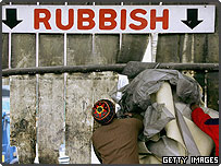 Two men loading rubbish into a local dump in London, England