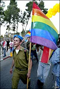 An Israeli soldier holds a rainbow-coloured flag at a gay pride parade in Jerusalem on 3 June 2004