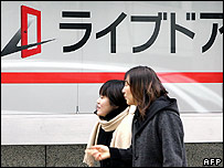 Pedestrians walk past Livedoor securities' office in Tokyo, 18 January 2006