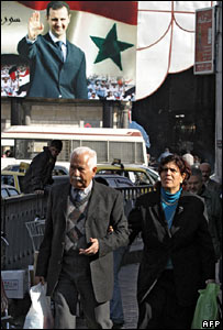 Syrians walk past a poster of Bashar al-Assad in Damascus