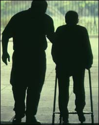 Carer helping old man walk, BBC