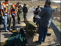 Israeli officials check the body of a settler killed near Hebron