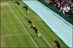 Groundsatff pull the rain covers across the courts