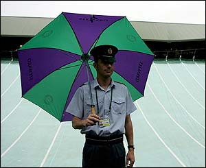 A Wimbledon steward shelters from the rain