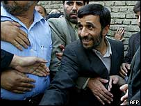 Mahmoud Ahmadinejad surrounded by bodyguards as he queues with ordinary Iranians outside a polling station