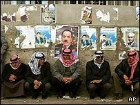 Palestinian men and election posters in the West Bank village of Hizme