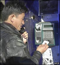 A man in Kathmandu tries calling from a public booth