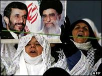 Iranian women at prayers holding pictures of Iranian President Mahmoud Ahmadinejad
