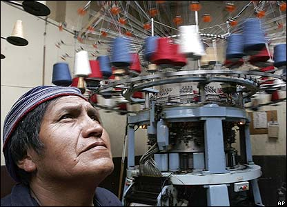 A worker stands in front of a spinning machine at the Punto Blanco factory in Bolivia