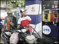 Man filling motor scooter at petrol station in Bangkok