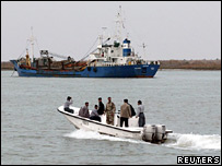Iraqi policemen approach a ship on the Shatt al-Arab