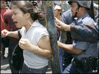 Riot police use their shields to push protesters away from Manila's Mendiola bridge near Malacanang Palace as they attempt to hold a rally Monday June 27, 2005