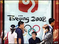 People walking past shop front with Beijing 2008 banner