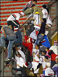 Sao Paulo fans climb over a fence during the recent match with River Plate