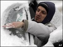 Житель Будапешта счищает снег с ветрового стекла автомобиля