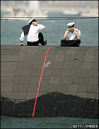 Two British submariners make mobile phone calls while sitting on the hull of the submarine HMS Trafalgar