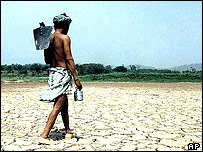 Indian farmer walking across dried out lake