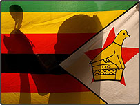 A young Zimbabwean girl holds a rose behind the national flag of her country, during a protest outside the Zimbabwean Embassy in central London (PA)