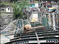 Residents crowd near a bridge over the Sutlej river in Himachal Pradesh damaged by flood waters.