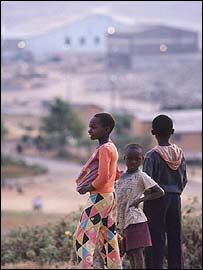 Children stand outside a Zambian copper mine